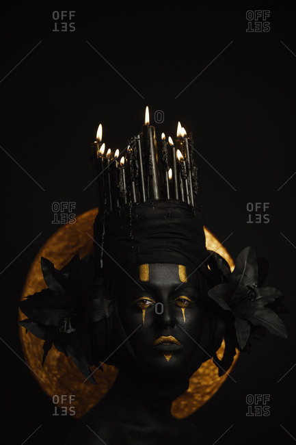Close up of a woman in black paint with yellow eyes, black lilies and a crown of burning black candles against a golden circle
