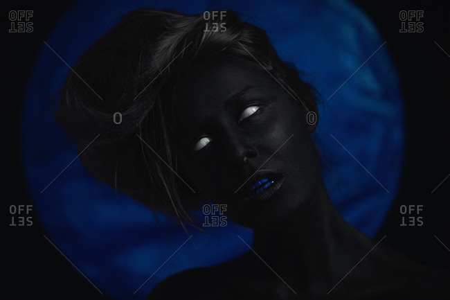 Close up of a woman painted in black with blue teeth against a blue background