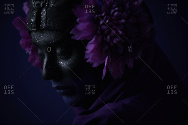 Close up of a woman painted in black wearing purple flowers and glitter against a purple background