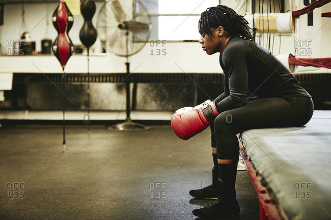 Side view of female boxer looking away while sitting at boxing gym