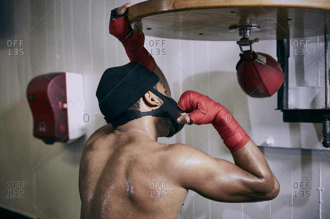 Rear view of shirtless male boxer hitting punching bag at health club