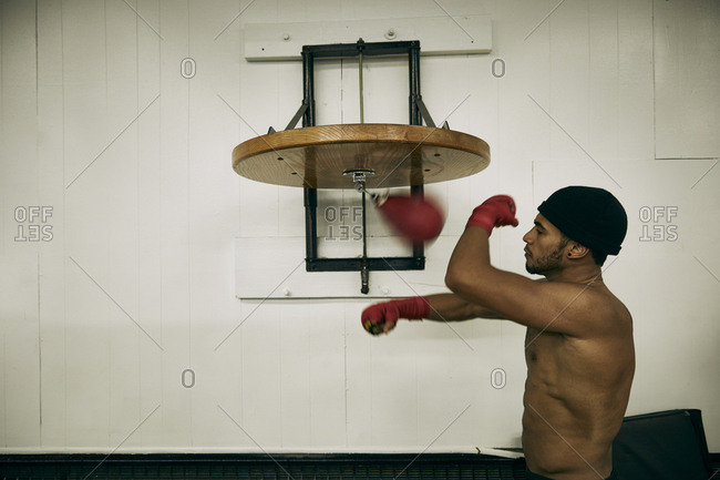 ... Side view of shirtless male boxer hitting punching bag at gym f7565d08c61