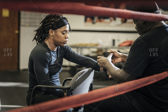Male coach wrapping bandage on female boxer's hand at gym