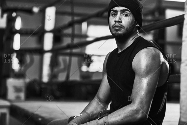 Portrait of confident male boxer sitting in boxing ring at health club