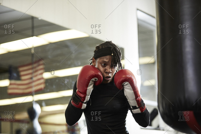 Determined female boxer practicing in health club