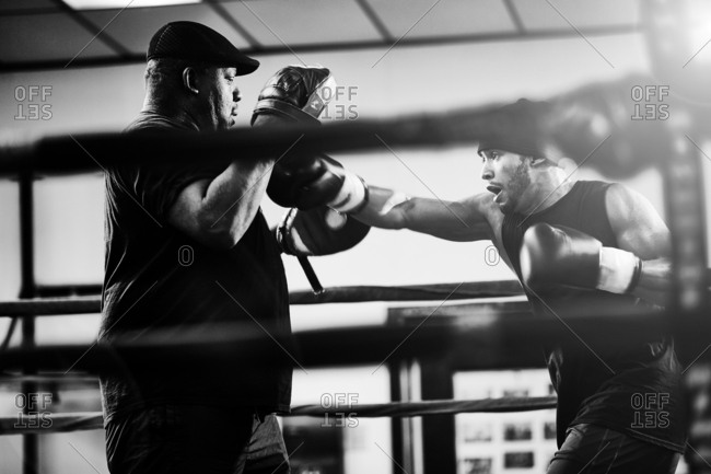 Determined male boxer practicing with coach in boxing ring at health club