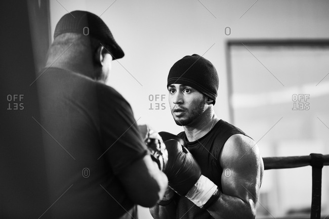 Determined boxer practicing with male coach in boxing ring at health club