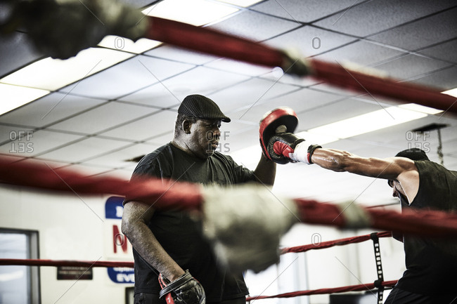 Determined male boxer practicing with coach in boxing ring at gym