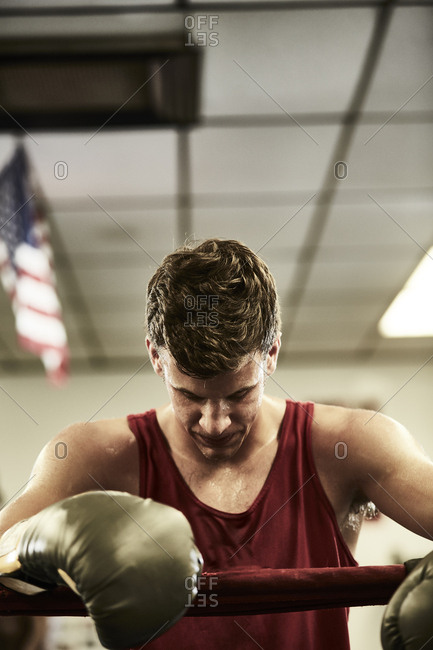 Exhausted male boxer standing in boxing ring at gym