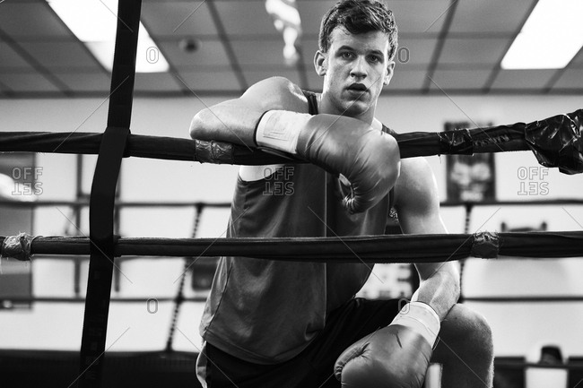 Portrait of confident male boxer in boxing ring at gym