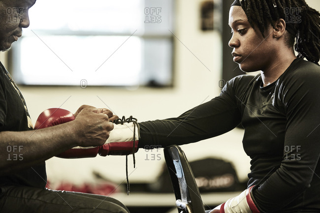 Male coach putting boxing glove on female boxer's hand at gym