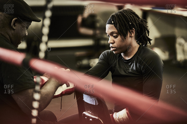 Male trainer putting boxing glove on female boxer's hand at gym