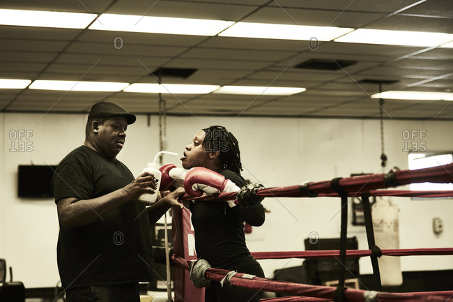 Side view of male coach feeding water to female boxer in boxing ring at health club