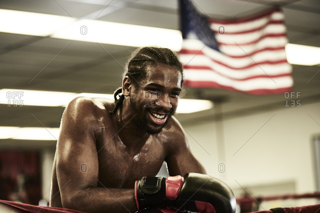 Happy male boxer looking away while standing in boxing ring at health club