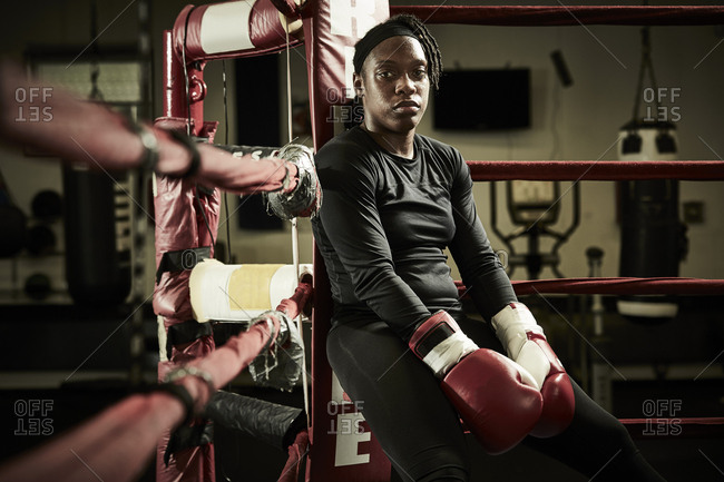 Portrait of tired female boxer sitting in boxing ring at health club