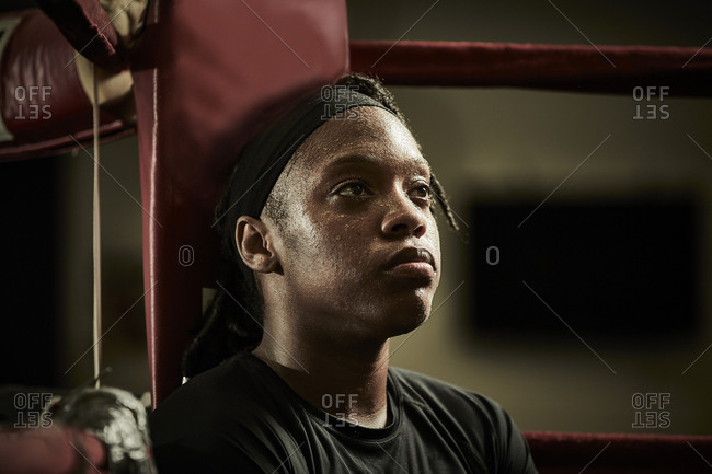 Tired female boxer looking away while sitting in boxing ring at health club