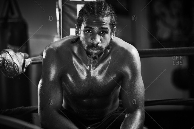 Portrait of confident male boxer sitting in boxing ring at gym