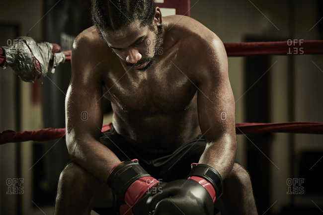 Tired male boxer sitting in boxing ring at health club