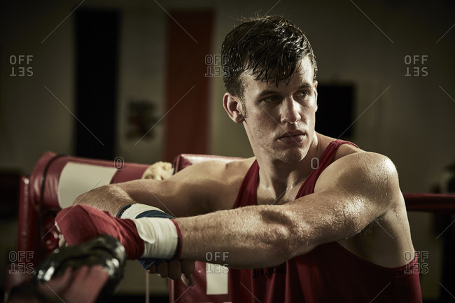 Thoughtful male boxer standing in boxing ring at health club