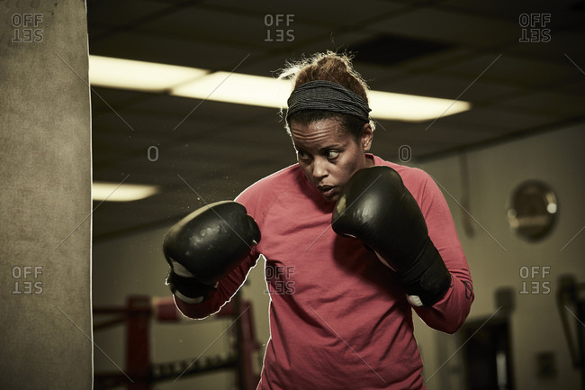 Determined female boxer practicing at health club