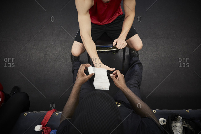 High angle view of coach wrapping bandage on male boxer's hand at health club