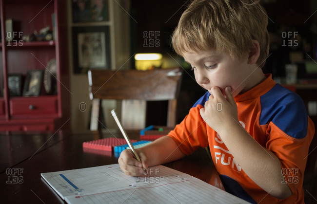 Boy at table writing in notepad
