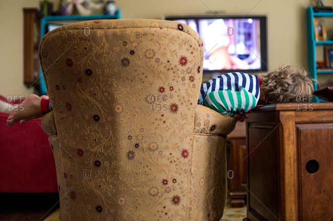 Boy sprawled across chair watching TV