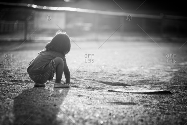 Girl touching dirt in baseball field
