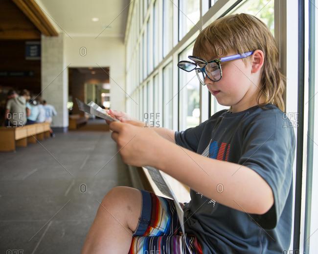Boy in pop up sunglasses reading brochure