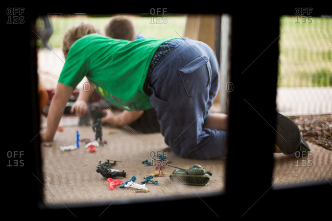 Boy playing with Army toys outside
