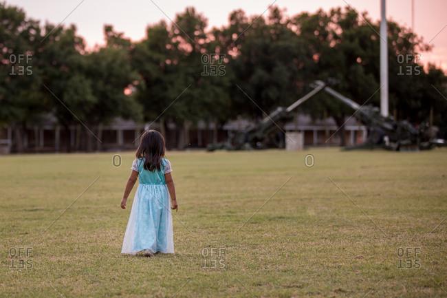 Girl in nightgown strolling in field