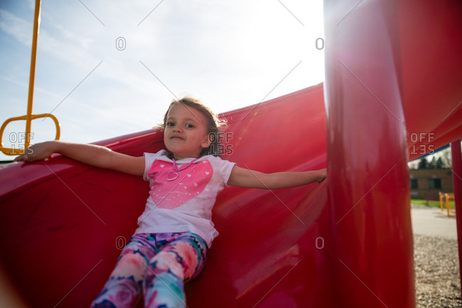 Girl going down a slide at the playground