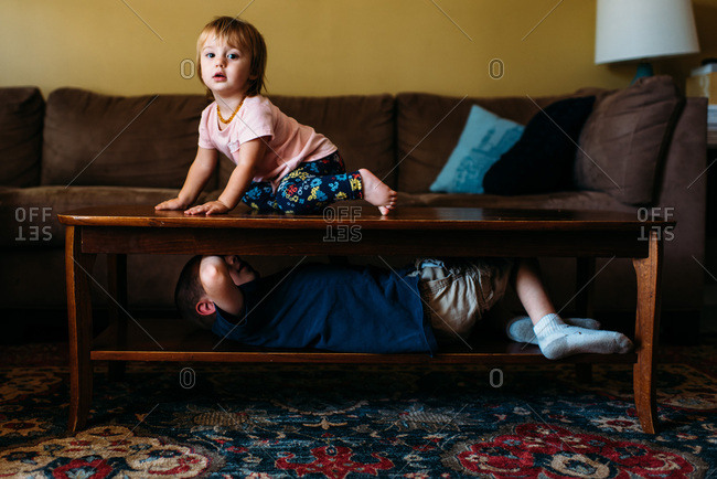 Little sister on top of table playing with big brother under table.