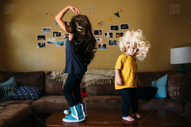 Sisters wearing wigs and dancing on a table at home.