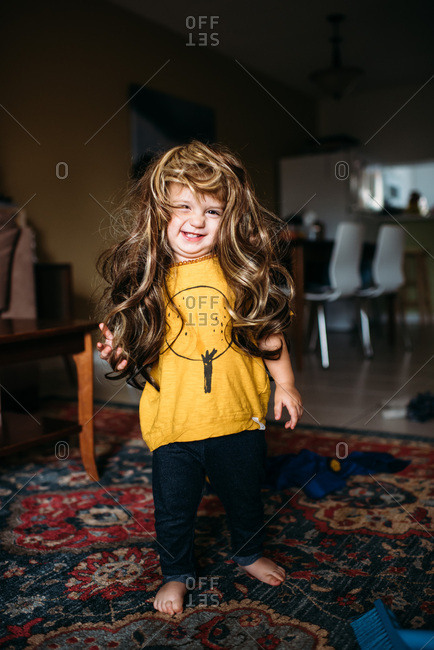 Toddler girl wearing yellow shirt and long brunette wig smiling and laughing.