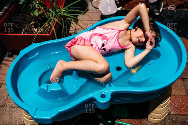 Young girl in bathing suit lying down in a play water table outside.