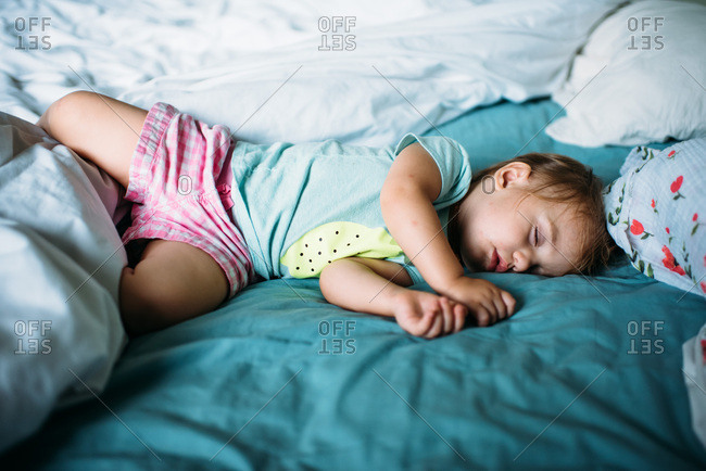 Toddler girl in shorts sleeping on parents' bed.
