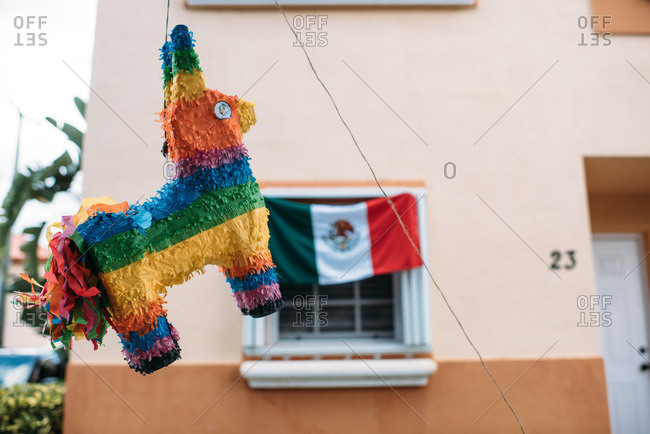 Colorful pinata hanging outside in front of a Mexican flag.