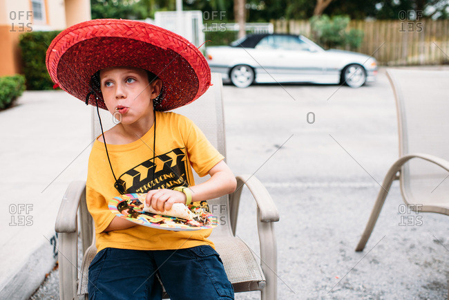 Boy in yellow shirt and red sombrero eating a burrito at a Cinco de Mayo celebration.