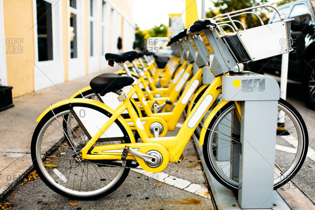 Yellow bikes lined up on street