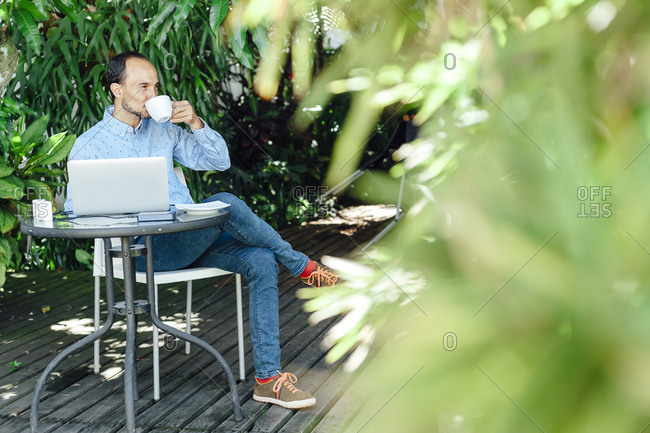 Remote worker man having a cup of coffee on a terrace in Medellin, Colombia