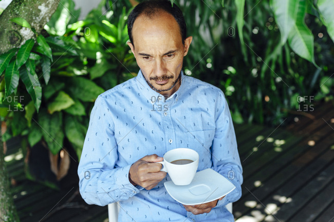 Portrait of a pensive mid aged man having a cup of coffee on a terrace of Medellin, Colombia