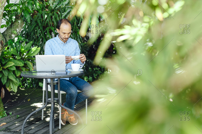 Remote worker man checking his camera on a terrace of Medellin, Colombia
