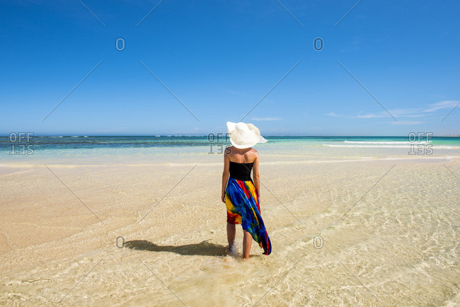 Turquoise Bay, Ningaloo Coast, Exmouth, Western Australia, Australia. Woman with straw hat and colored dress walking on the beach