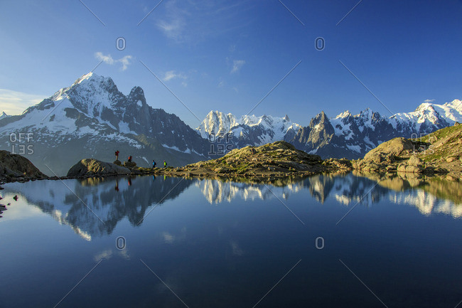 Photographers and hikers on the shore of Lac De Cheserys at dawn Haute Savoie France Europe