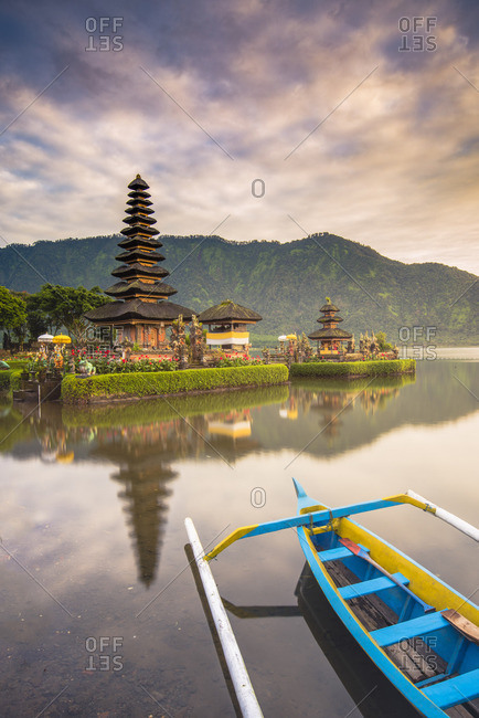 Bali, Indonesia, South East Asia. The Pura Ulun Danu Bratan water temple and a traditional Indonesian canoe (cadik or jukung) moored on the Lake Bratan.