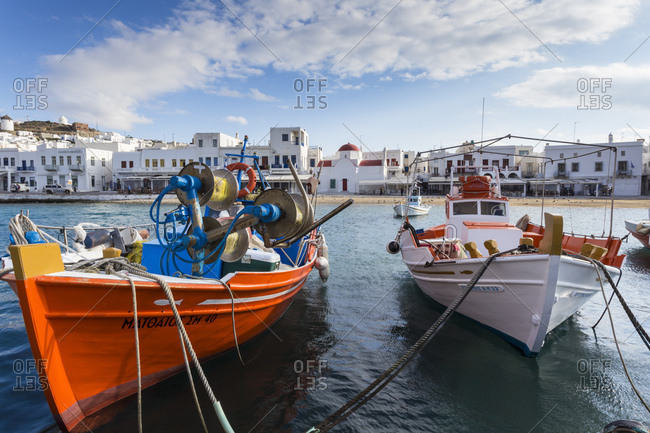 Mykonos, Greece - November 16, 2016: Colorful boats in harbor, whitewashed Mykonos Town (Chora) with windmills and churches