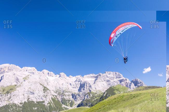 Trentino-Alto Adige, Italy - July 16, 2016: A paraglider among rocky peaks and green meadows Doss Del Sabion, Pinzolo, Brenta Dolomites, Trentino-Alto Adige, Italy, Europe