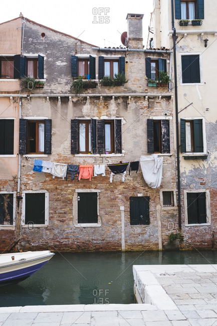 Clothing hanging outside a home over canal, Venice, Italy