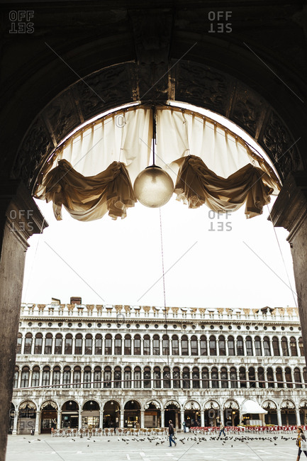 Arch with hanging light with a view of Saint Mark's Square, Venice, Italy